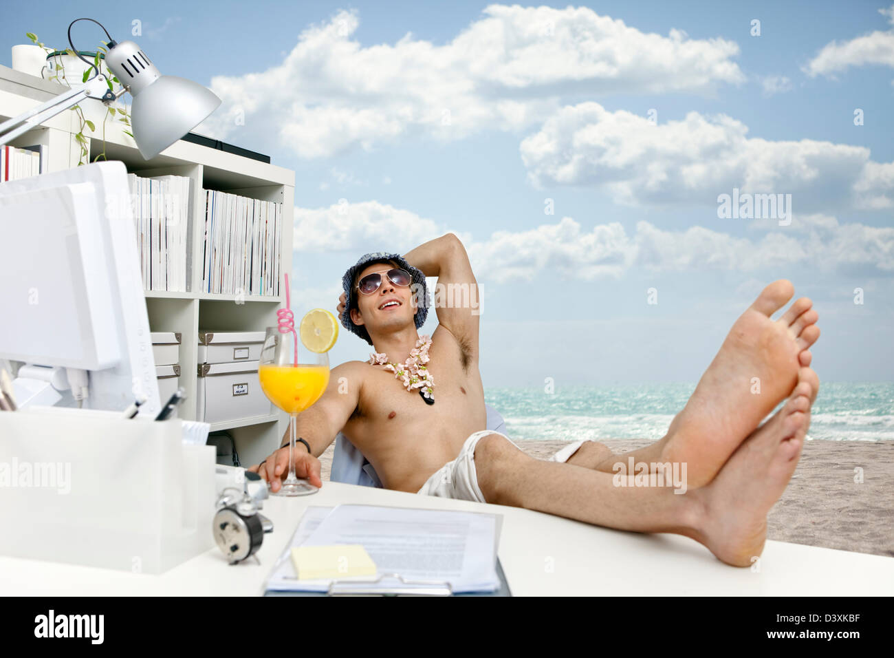 junger Mann bei Arbeit Tagträumen über Strand, Cocktails und leichten Leben Stockbild
