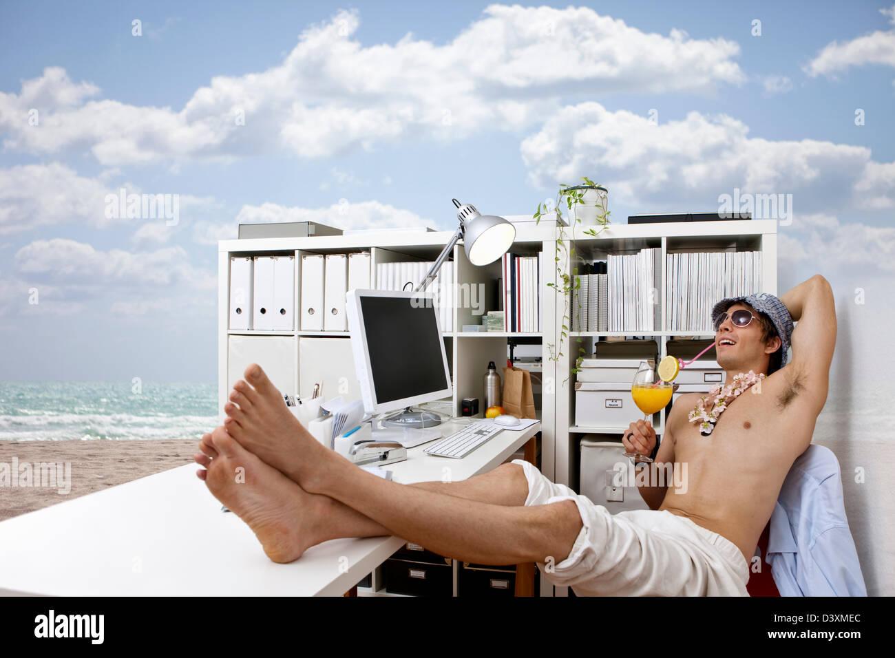 junger Mann bei Arbeit Tagträumen über Strand, Cocktails, leichtes Leben Stockbild