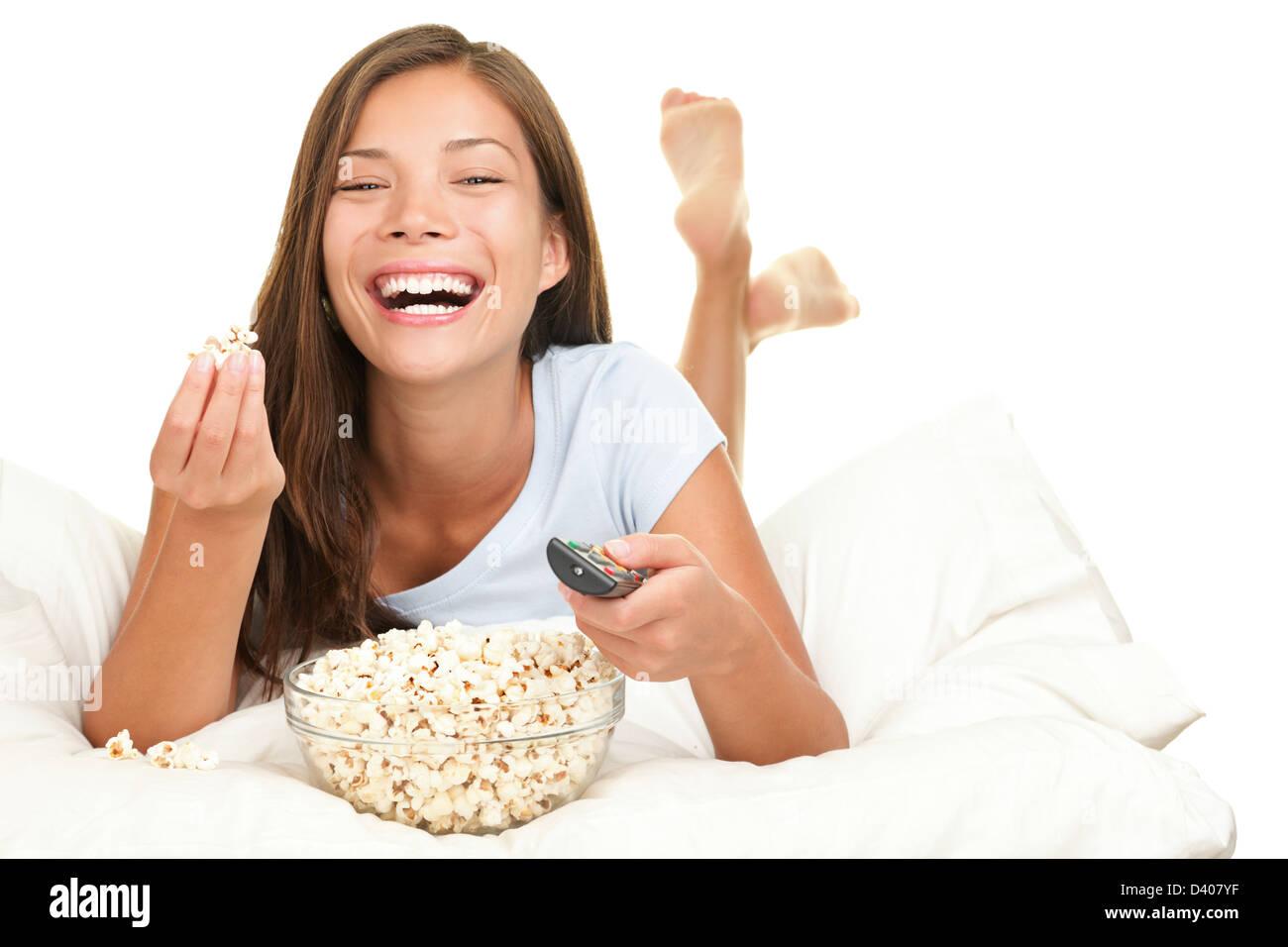 fr hliche junge mischlinge kaukasier asiatische frau vor dem fernseher beim essen popcorn im. Black Bedroom Furniture Sets. Home Design Ideas
