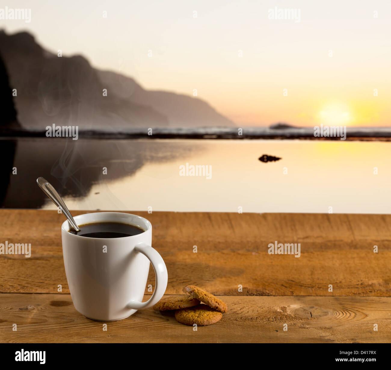Tasse Kaffee auf einem Tisch bei Sonnenauf- oder Sonnenuntergang Blick auf eine wunderschöne Landschaft Stockbild
