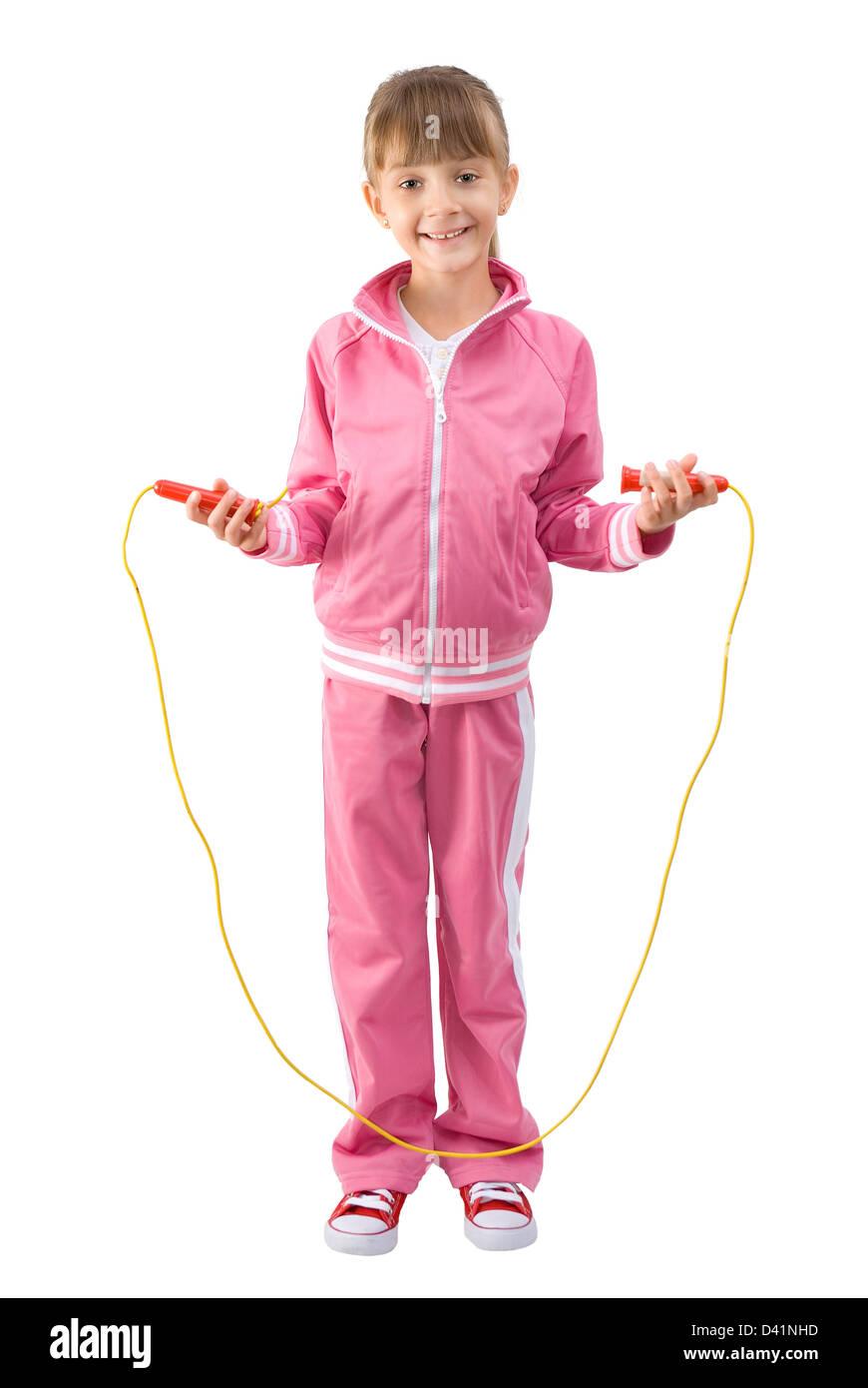 Das kleine Mädchen in einem rosa Sport Anzug springt durch ein Springseil Stockfoto