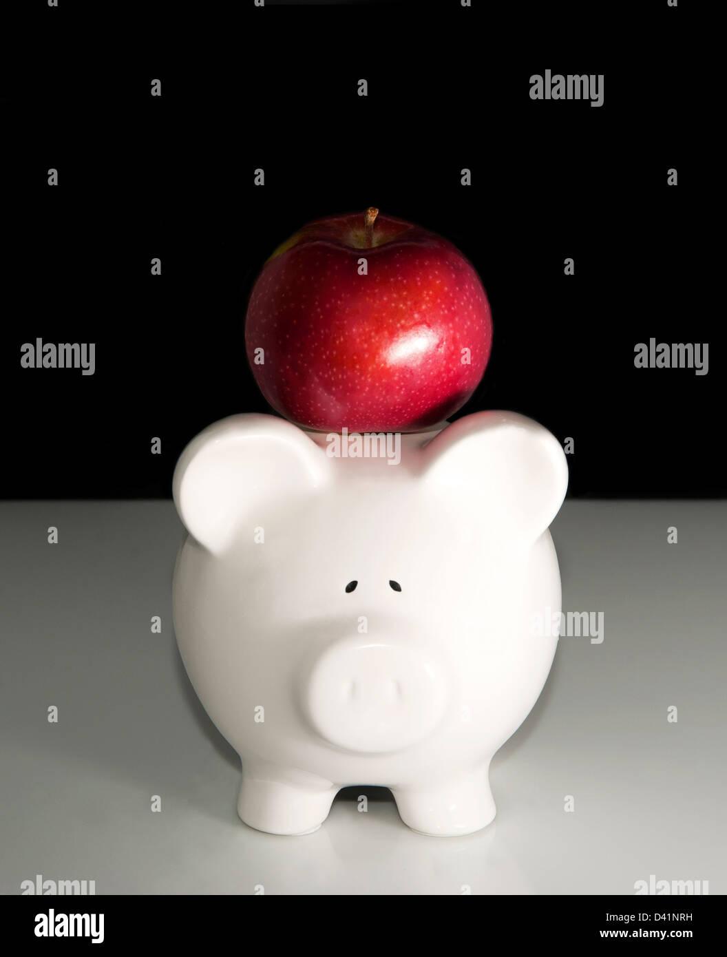 Sparschwein mit Apfel auf den Kopf Stockbild