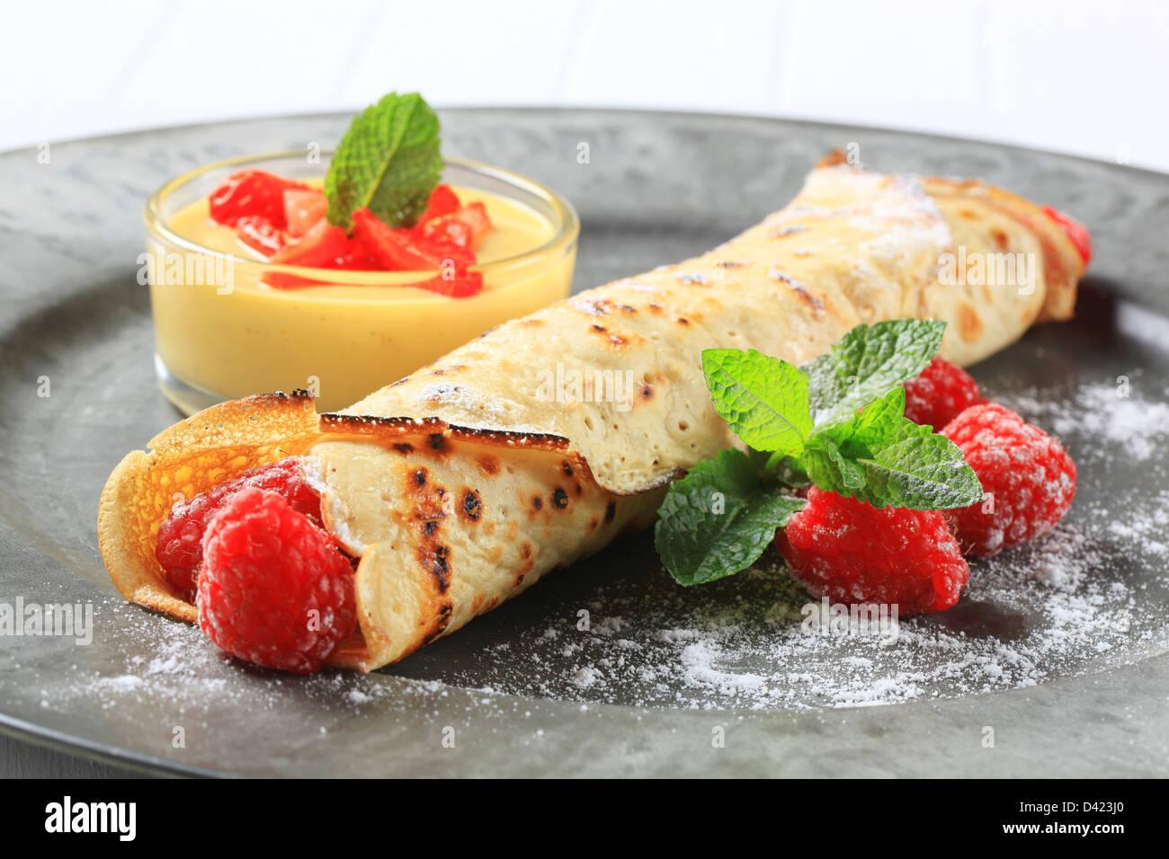 Crêpe gefüllt mit frischen Himbeeren und Sahne Pudding Stockbild