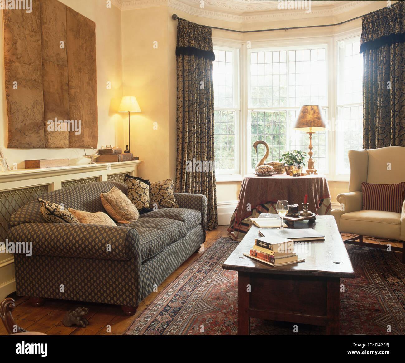 Große Graue Gemustertes Sofa Unter Abstrakter Malerei Im Traditionellen  Wohnzimmer Mit Niedrigen Holzkiste Und Grau Drapiert Auf Erker