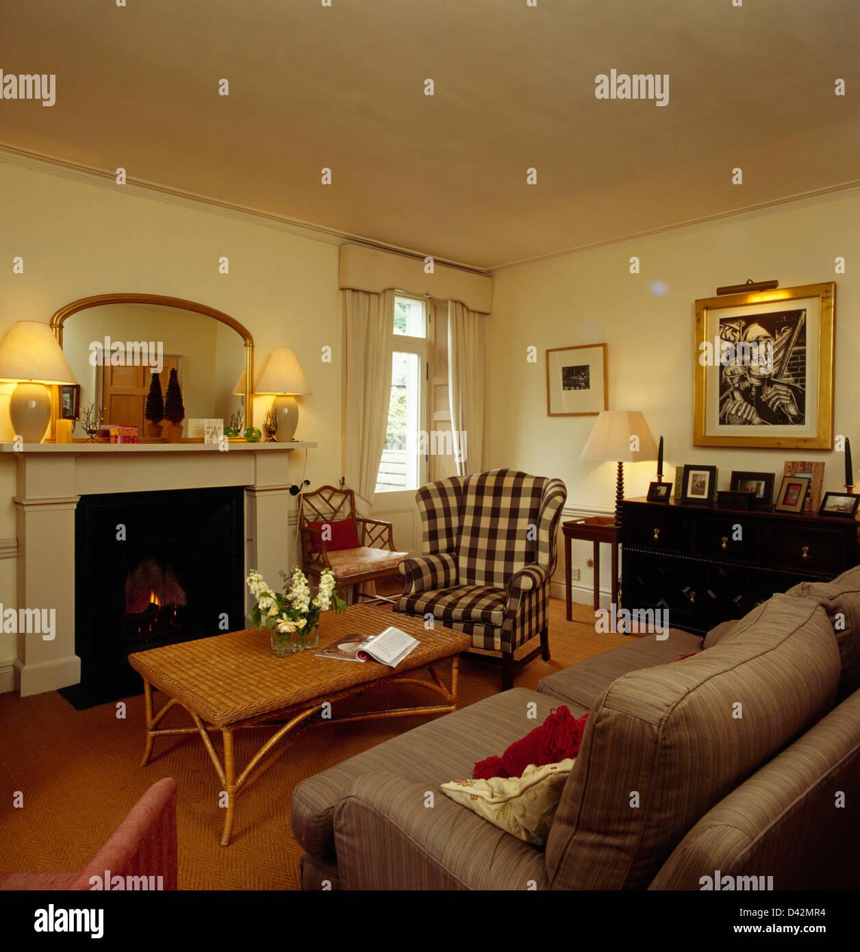 Lampen und Spiegel auf Kaminsims im Wohnzimmer mit Peddigrohr ...