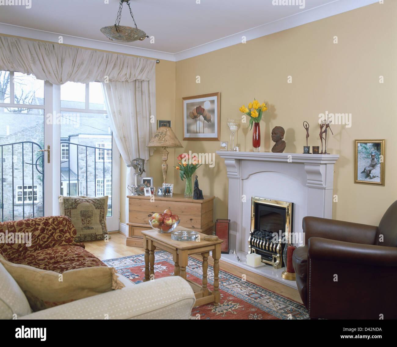 Creme Sofa Und Braunem Lederstuhl Neben Kamin Im Ersten Stock Wohnung  Wohnzimmer Mit Cremefarbenen Vorhängen Auf Französische Fenster