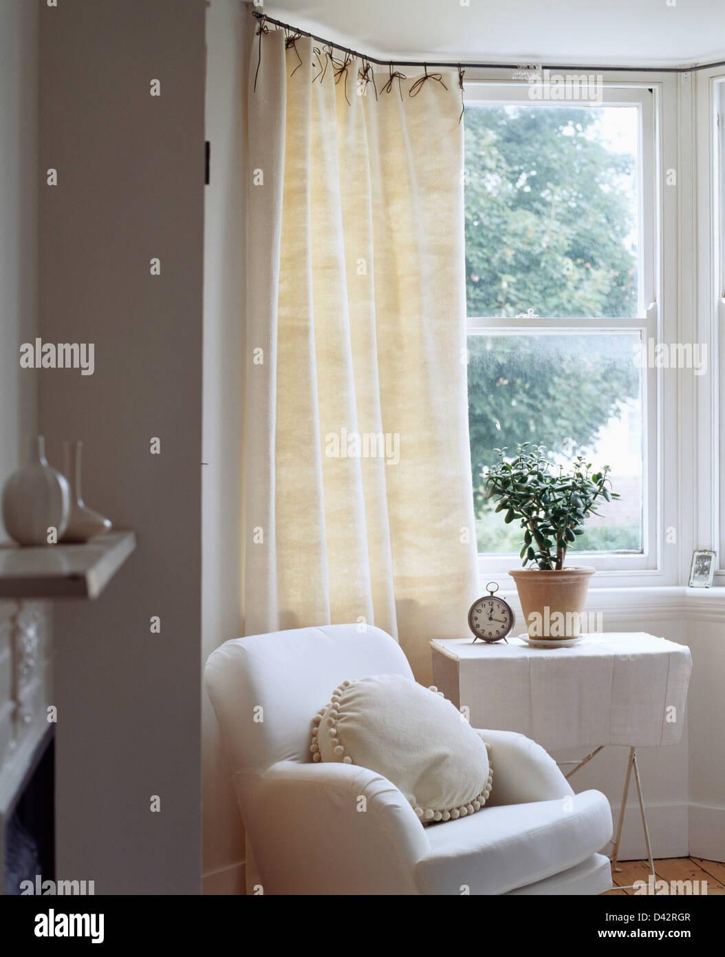 Weißer Sessel und Beistelltisch mit weißen Tuch vor Erker mit Creme ...