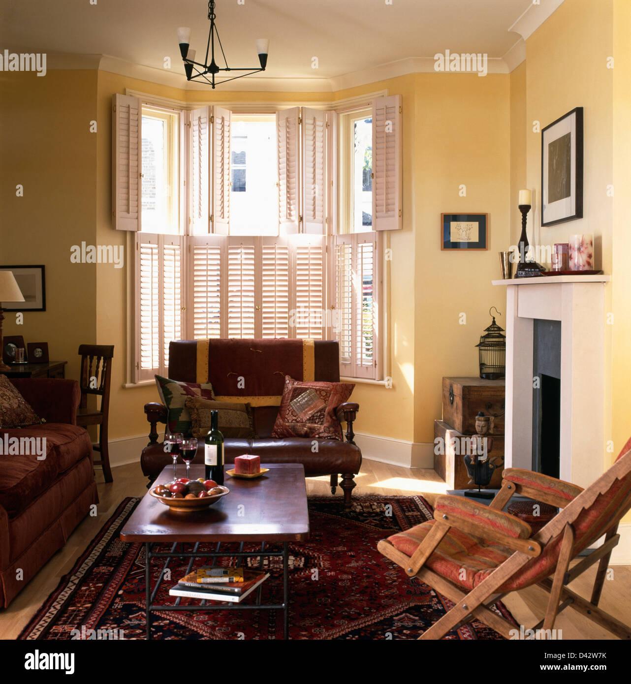 Kleine Braune Ledercouch Unter Fenster Mit Plantage Fensterläden Im  Wohnzimmer Mit Couchtisch Auf Orientteppich
