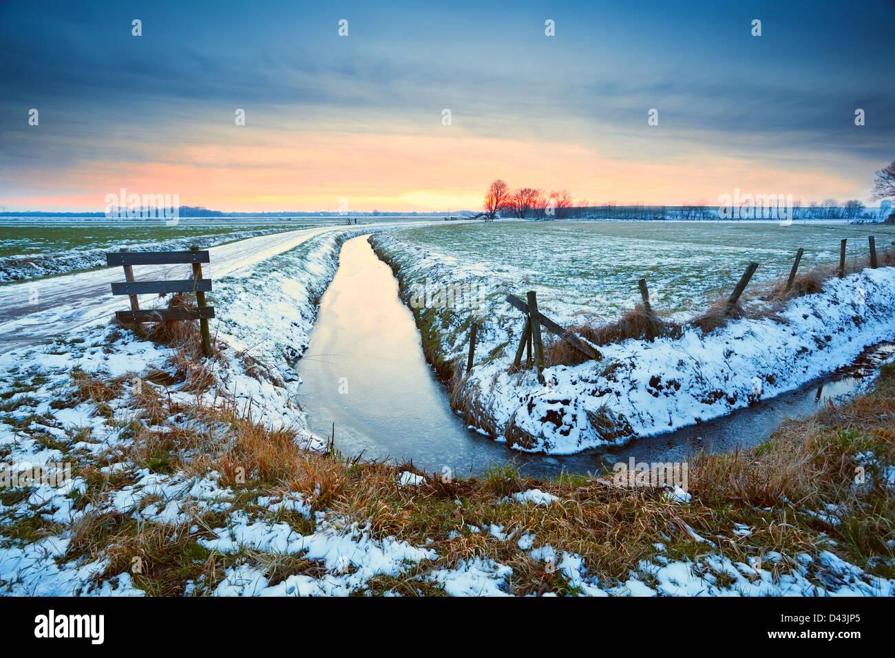dramatischen Sonnenuntergang über den zugefrorenen Fluss im niederländischen Ackerland Stockbild