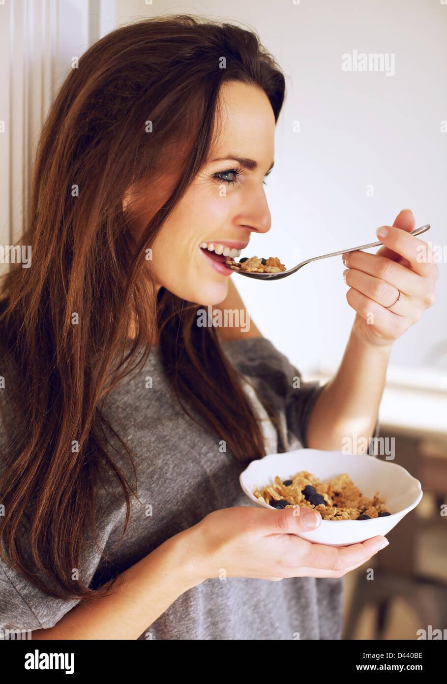 Porträt einer lächelnden Frau Essen zu Hause ihr Frühstück Stockbild