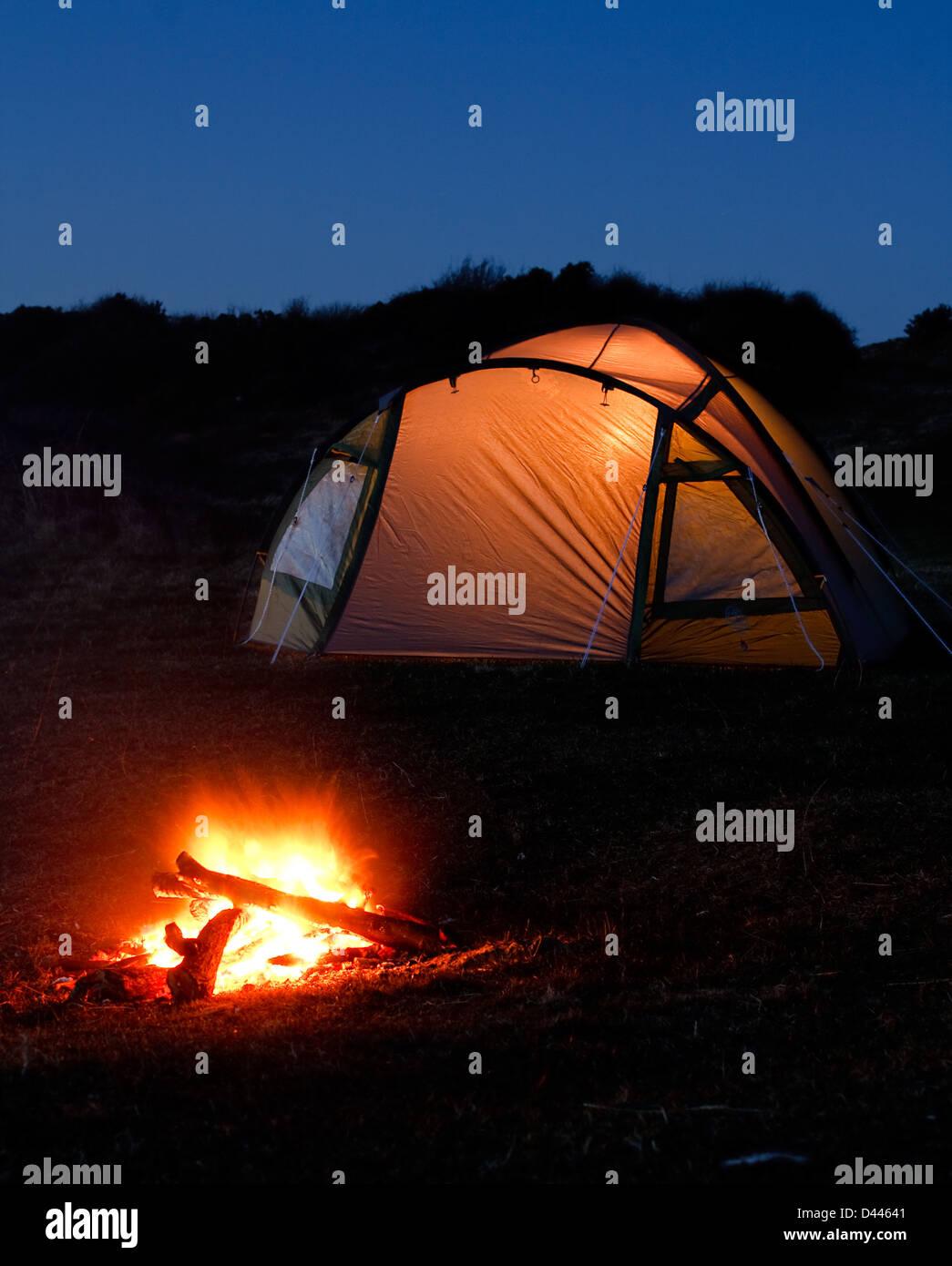 Zelt leuchtet in der Nacht mit Lagerfeuer vor symbolisiert camping Urlaub oder Ferien auf dem Land Stockbild