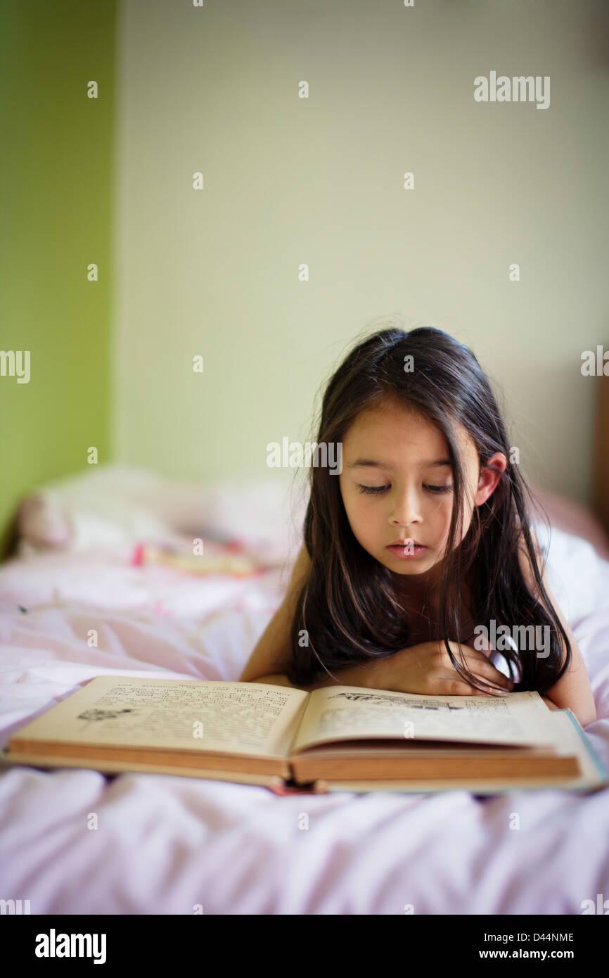 Mädchen liegt im Bett und Las Buch Stockbild