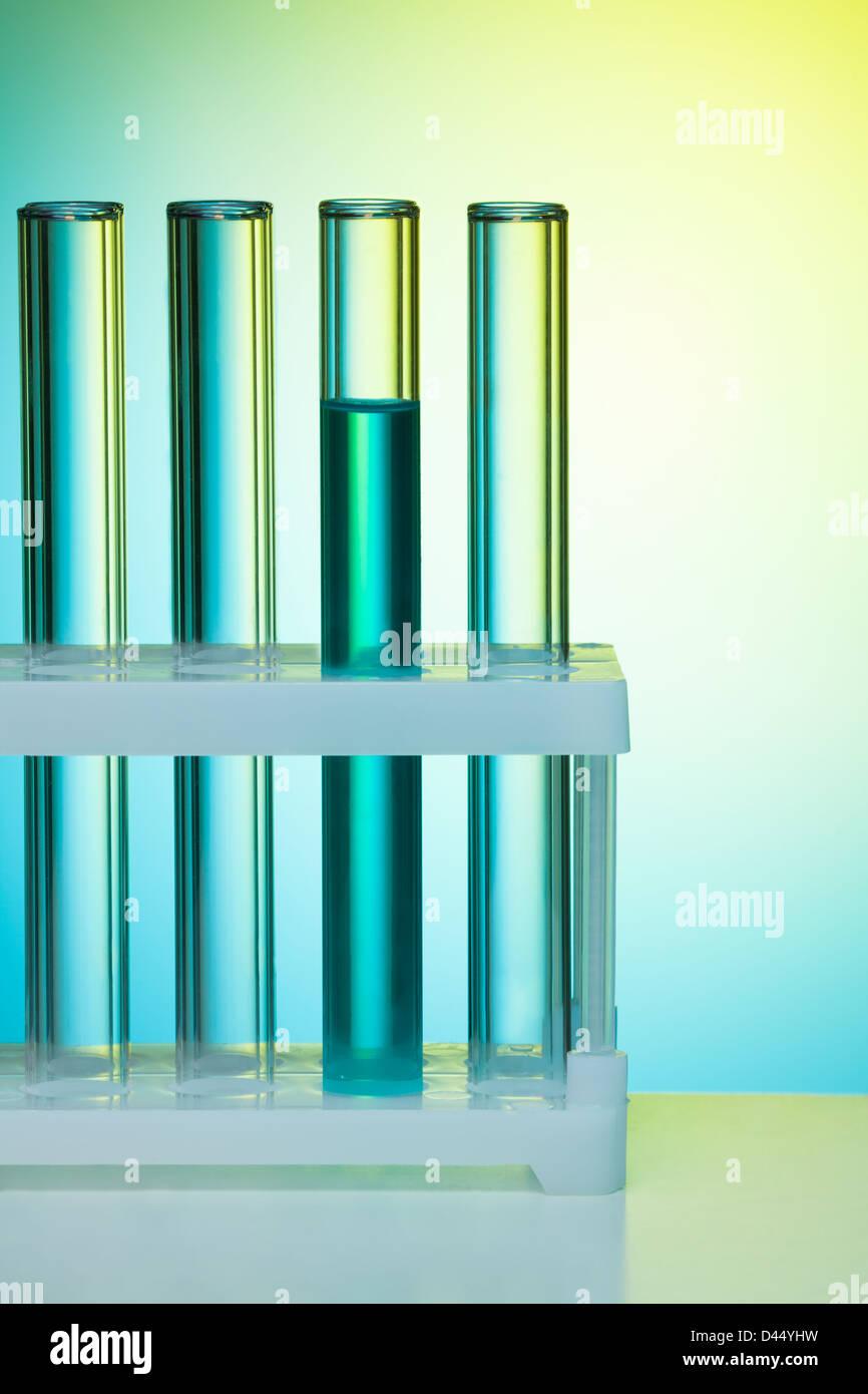 Eine Reihe von Reagenzgläsern auf blauem Hintergrund im Labor Stockbild