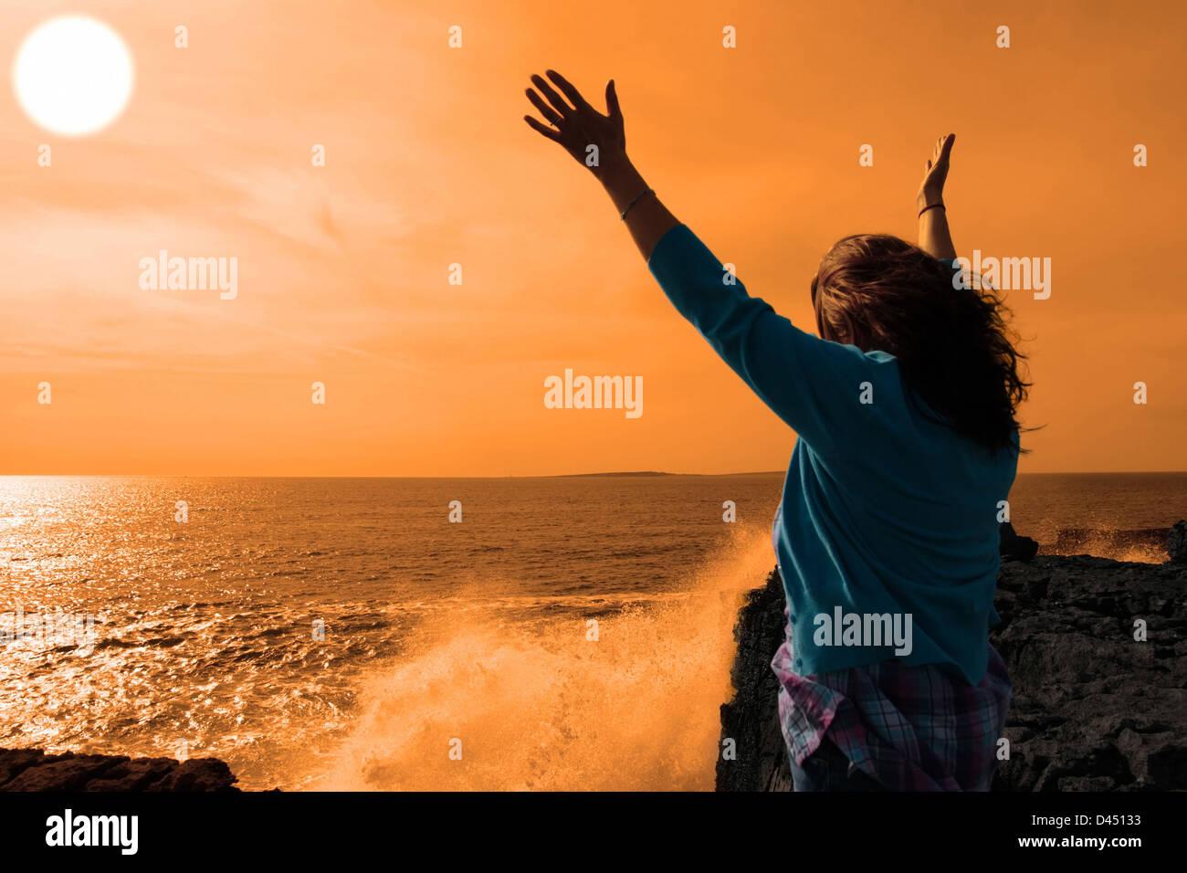 eine einsame Frau, hob die Arme in Ehrfurcht vor den mächtigen Wellen am Rande der Klippen in County Clare Irland Stockfoto
