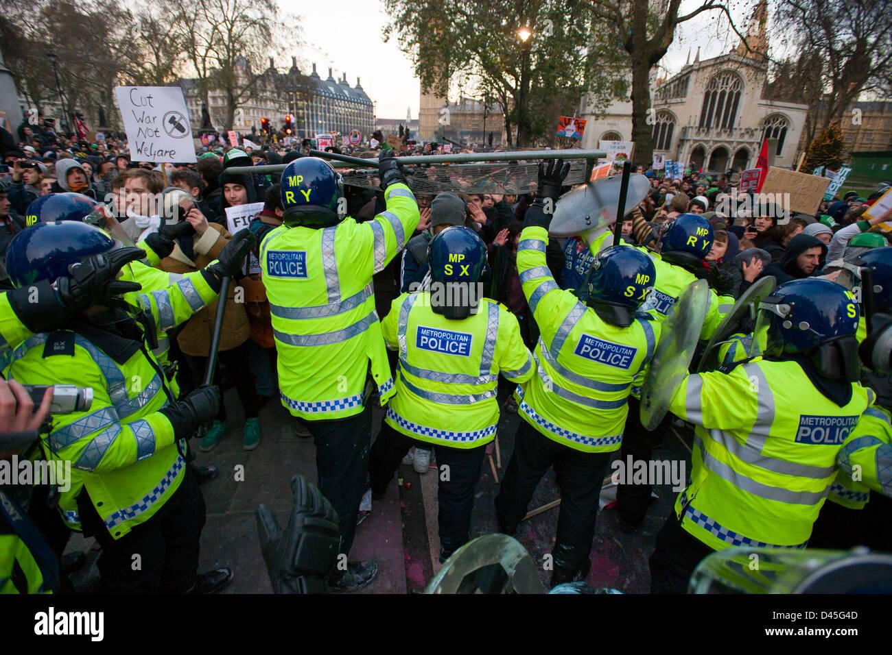 Protestierende Studenten Angriff auf eine dünne Linie der Polizei in voller Aufruhr Getriebe mit einer Menge Stockbild