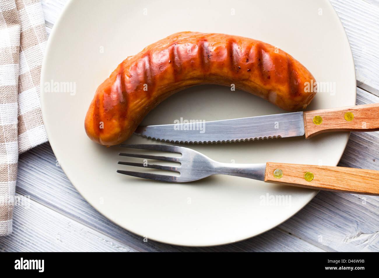 gegrillten Würstchen auf Teller mit Besteck Stockbild