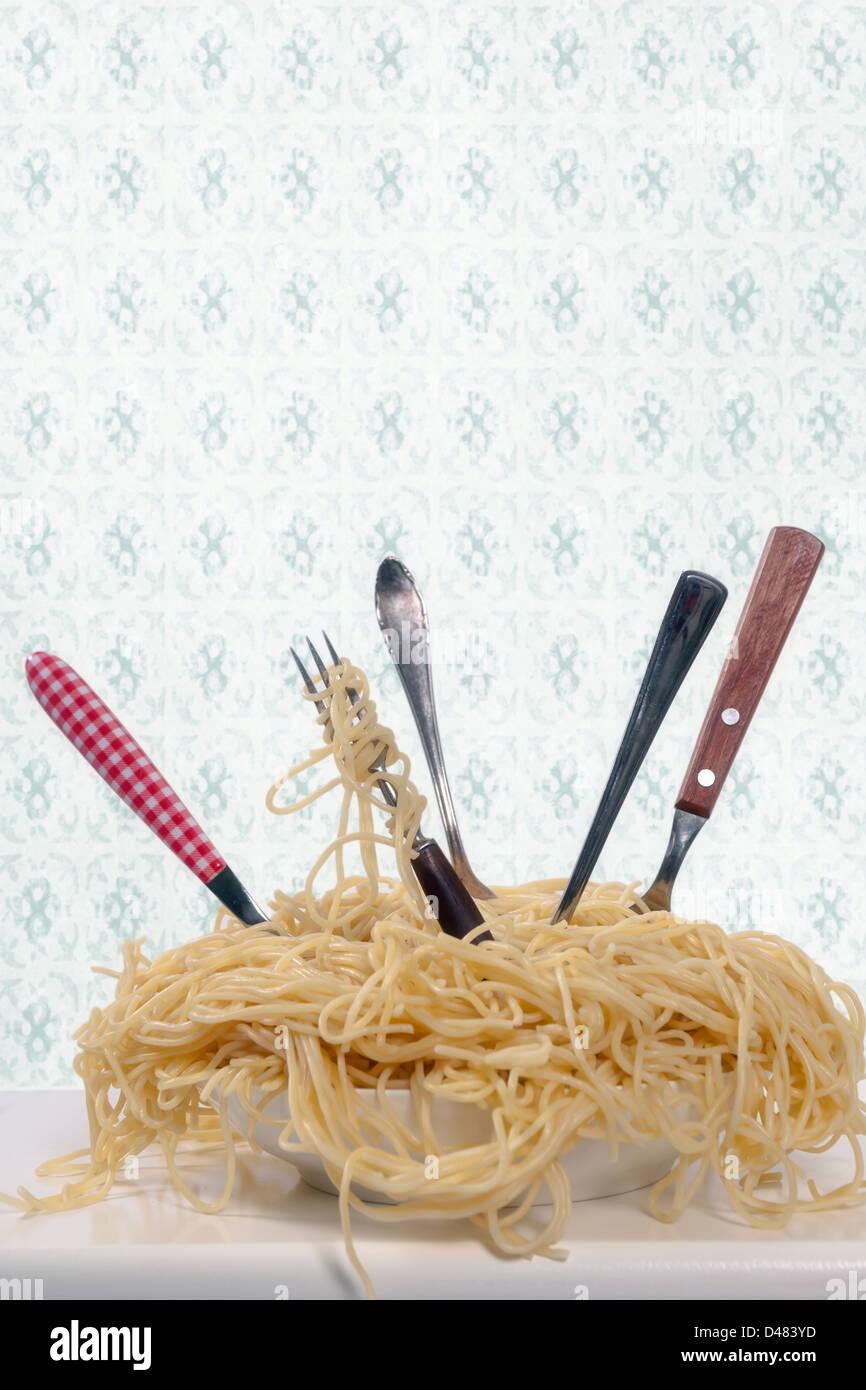 ein Teller voll Spaghetti mit fünf Gabeln Stockfoto