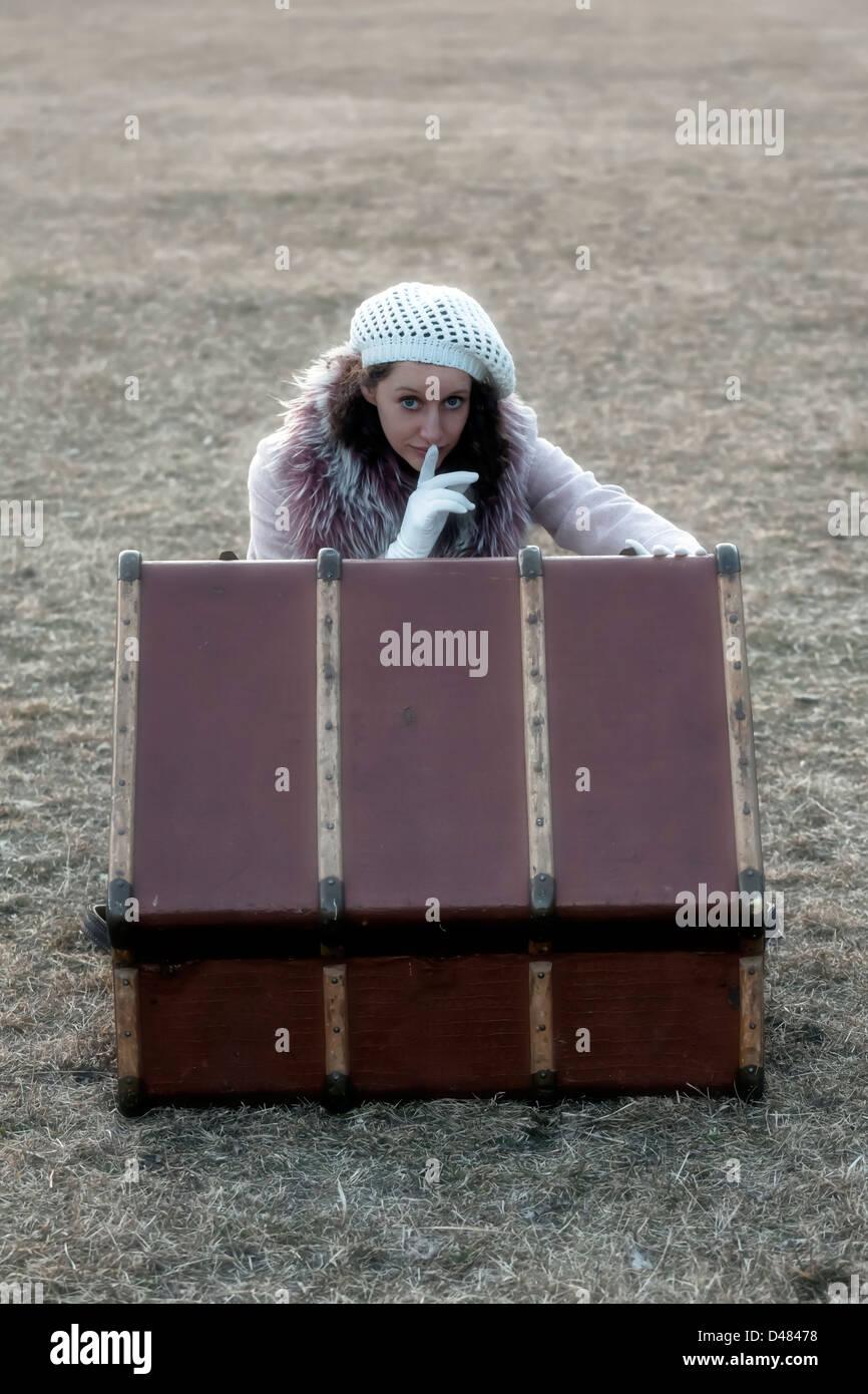 eine Frau hat etwas Geheimnisvolles in einem alten Koffer gefunden. Stockbild