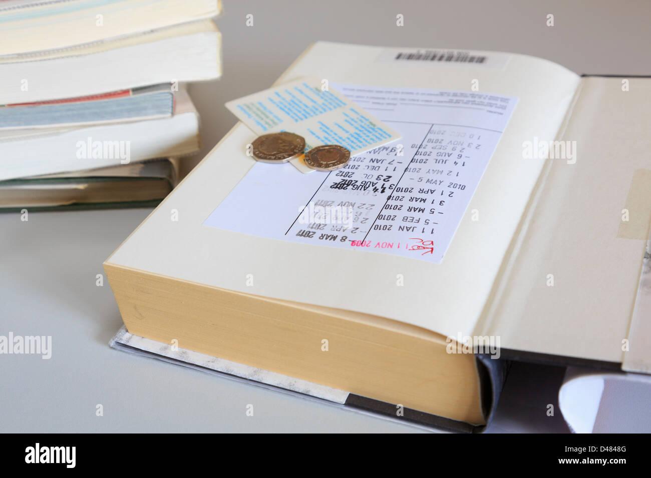 Bibliothek Buch öffnen auf der ersten Seite mit Terminen versehen, einen Mitgliedsausweis und Münzen für Stockbild