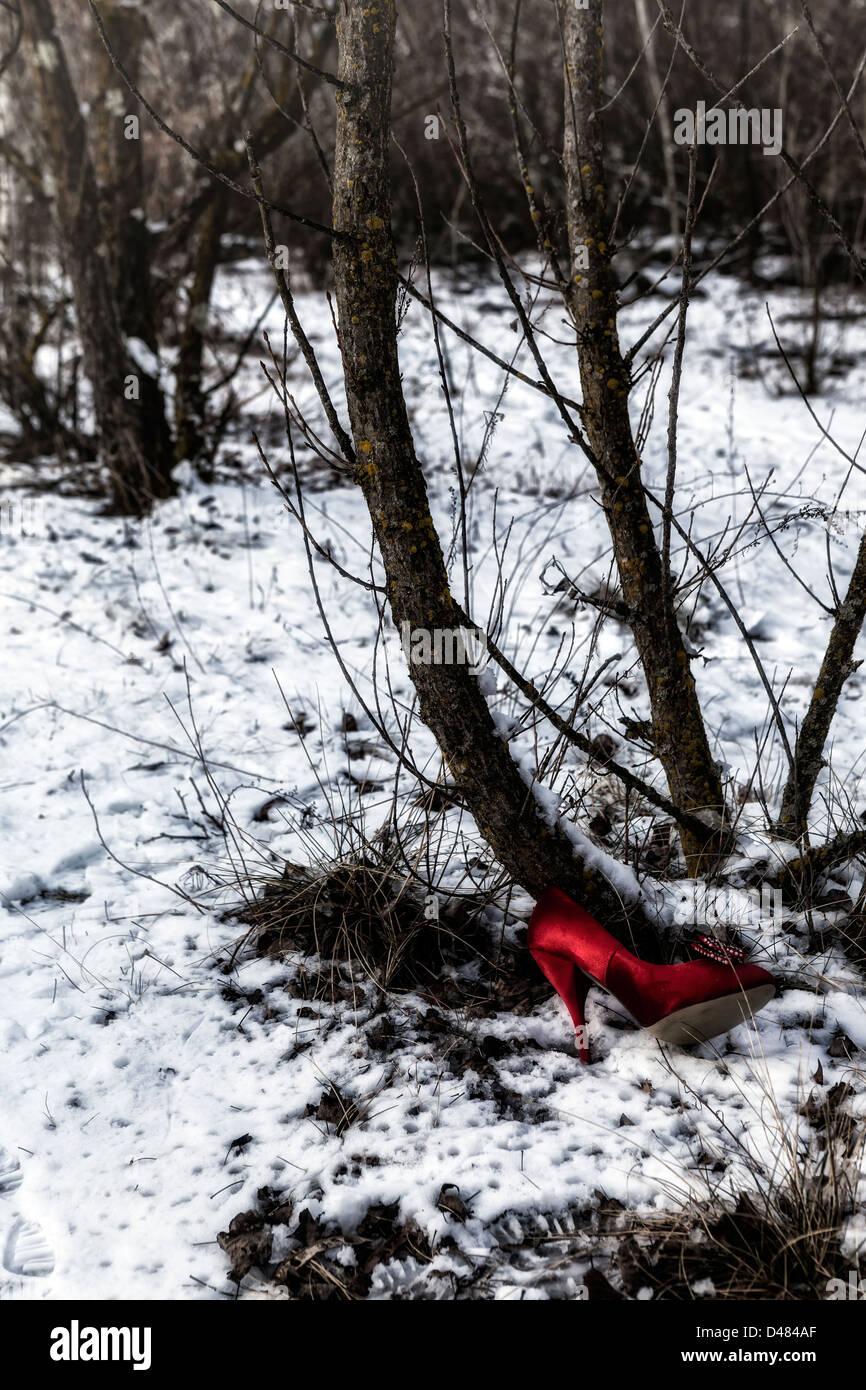 eine rote Frau Schuh, in den Wäldern im Schnee verloren Stockbild