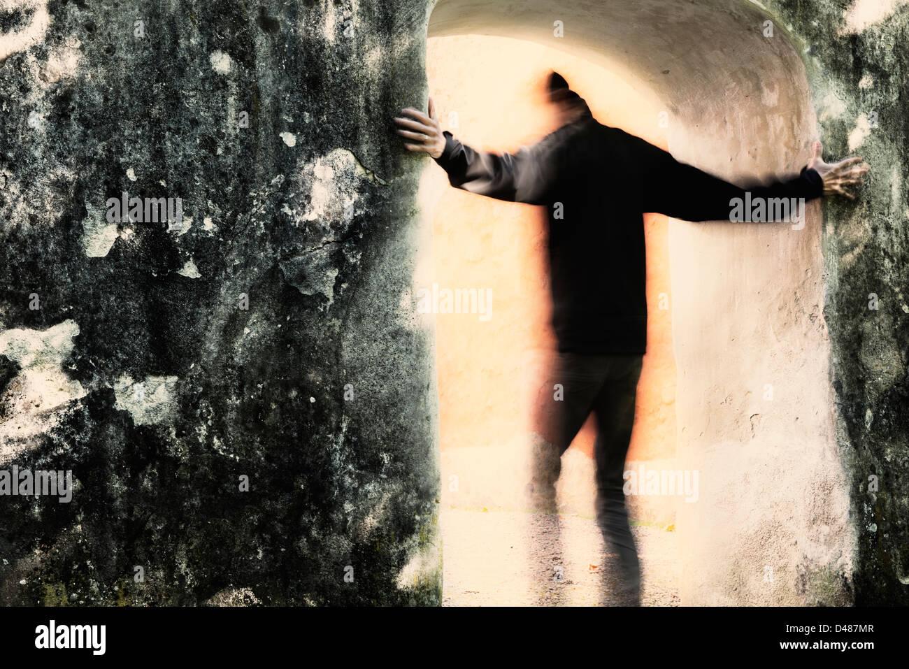 Männchen aus der Dunkelheit ins Licht durch Portal bewegen. Er hält an der Steinmauer. Stockbild
