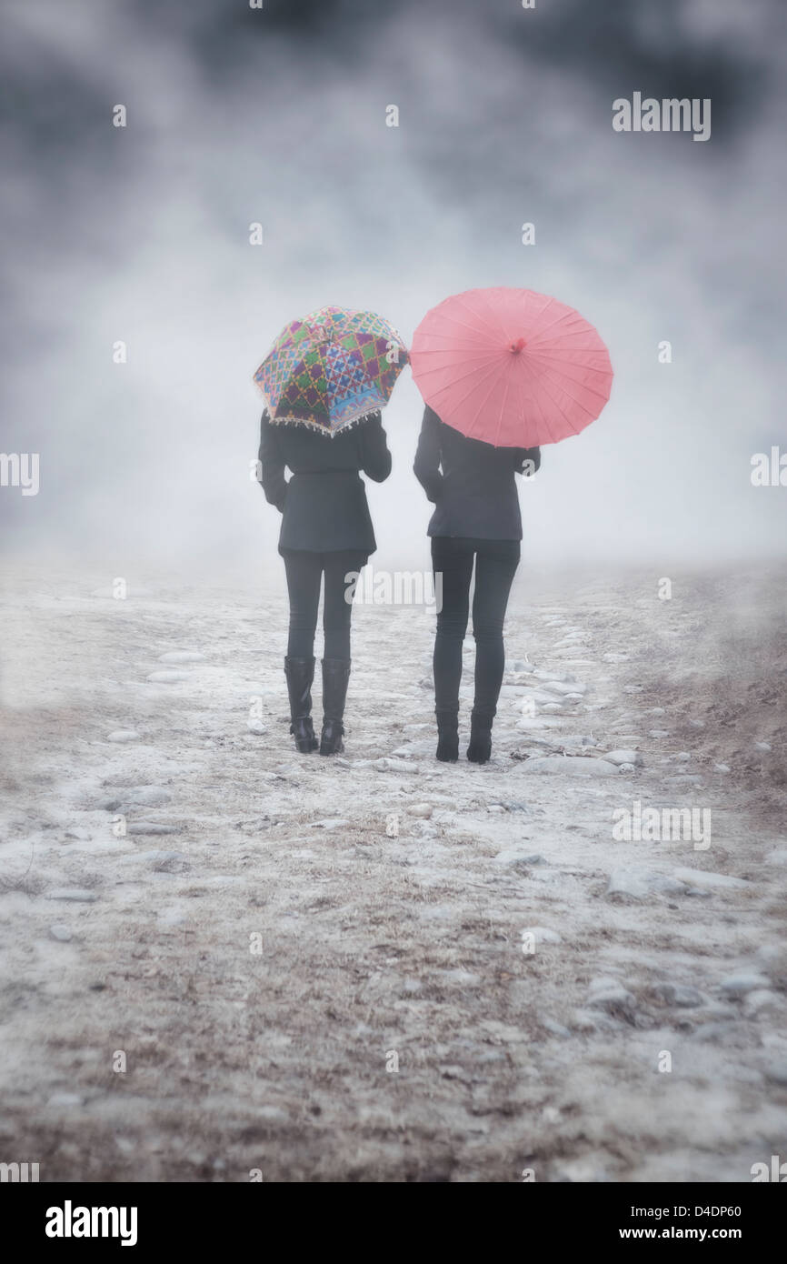 zwei Mädchen mit bunten Sonnenschirmen sind im Nebel wandern. Stockbild