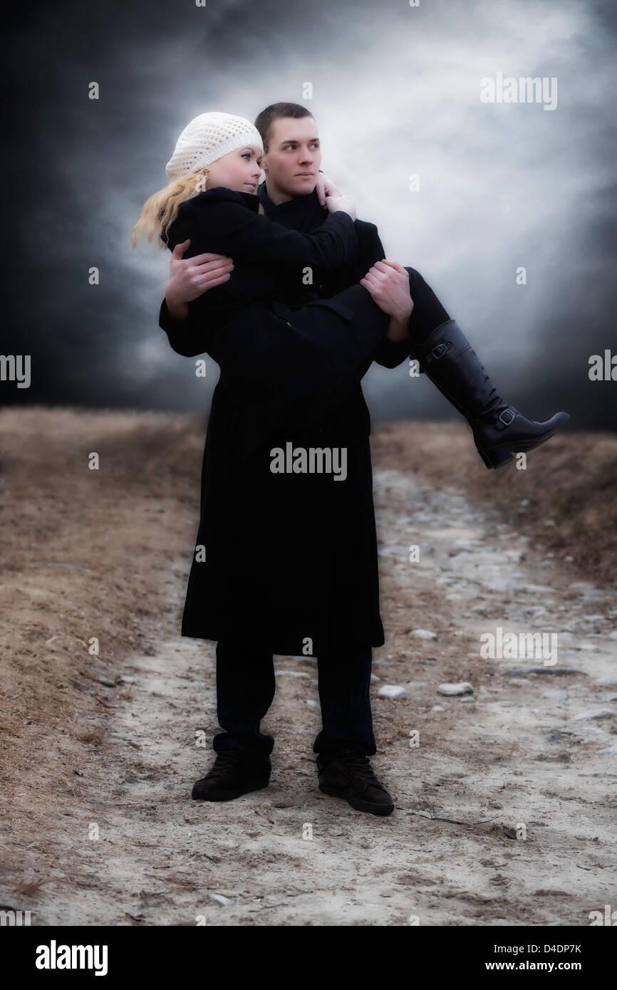 ein Mann trägt seine Freundin über eine Wiese Stockbild