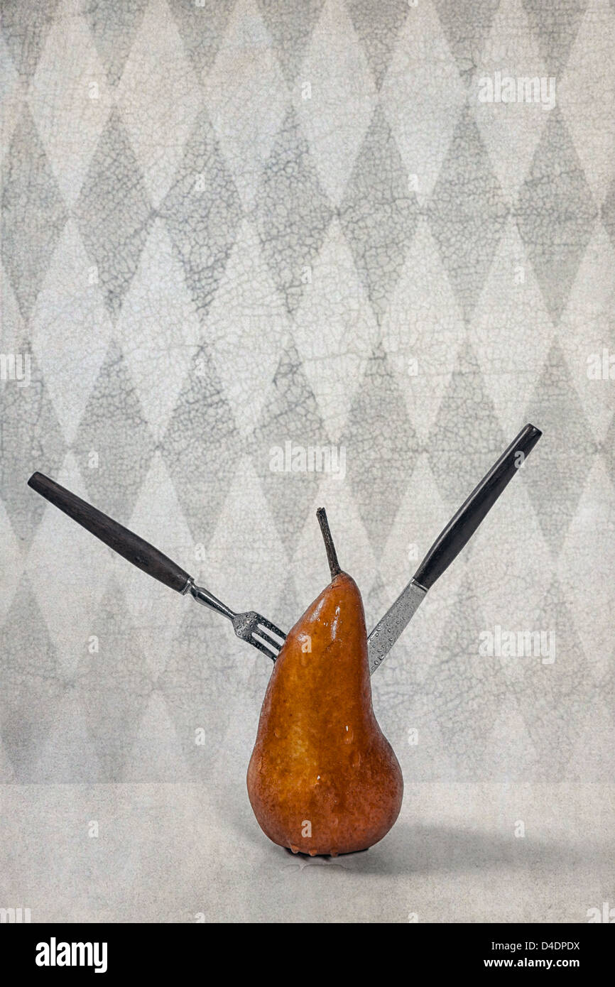 eine Birne mit einer Gabel und einem Messer durchbohrt Stockbild