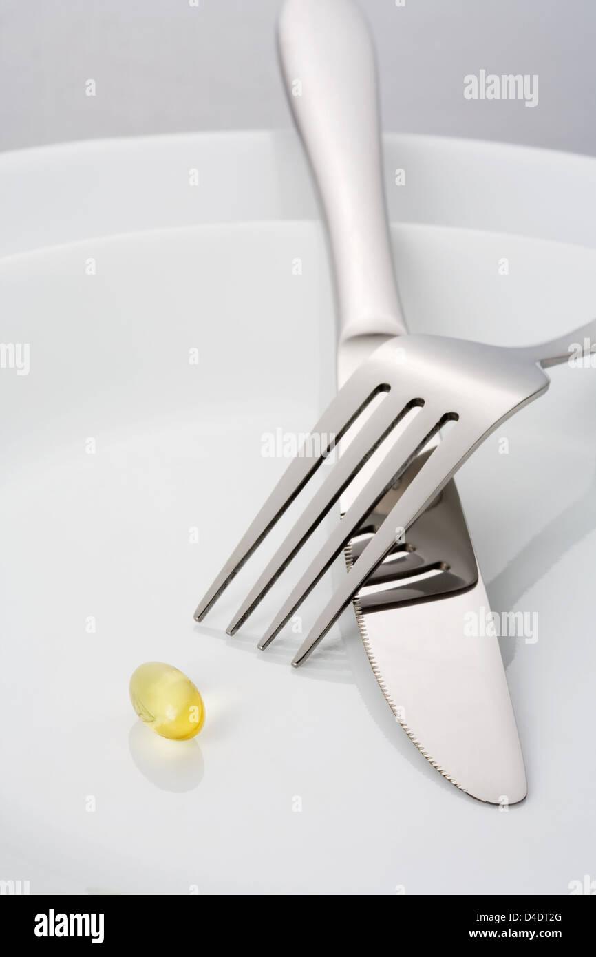 Gabel, Messer und ein einzelner Fisch Öl Kapsel auf einer Platte Stockbild