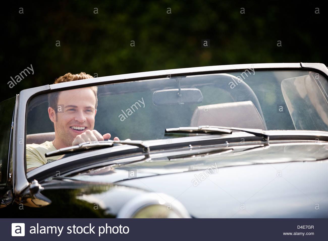 Ein junger Mann, ein schwarzer Sportwagen Stockbild