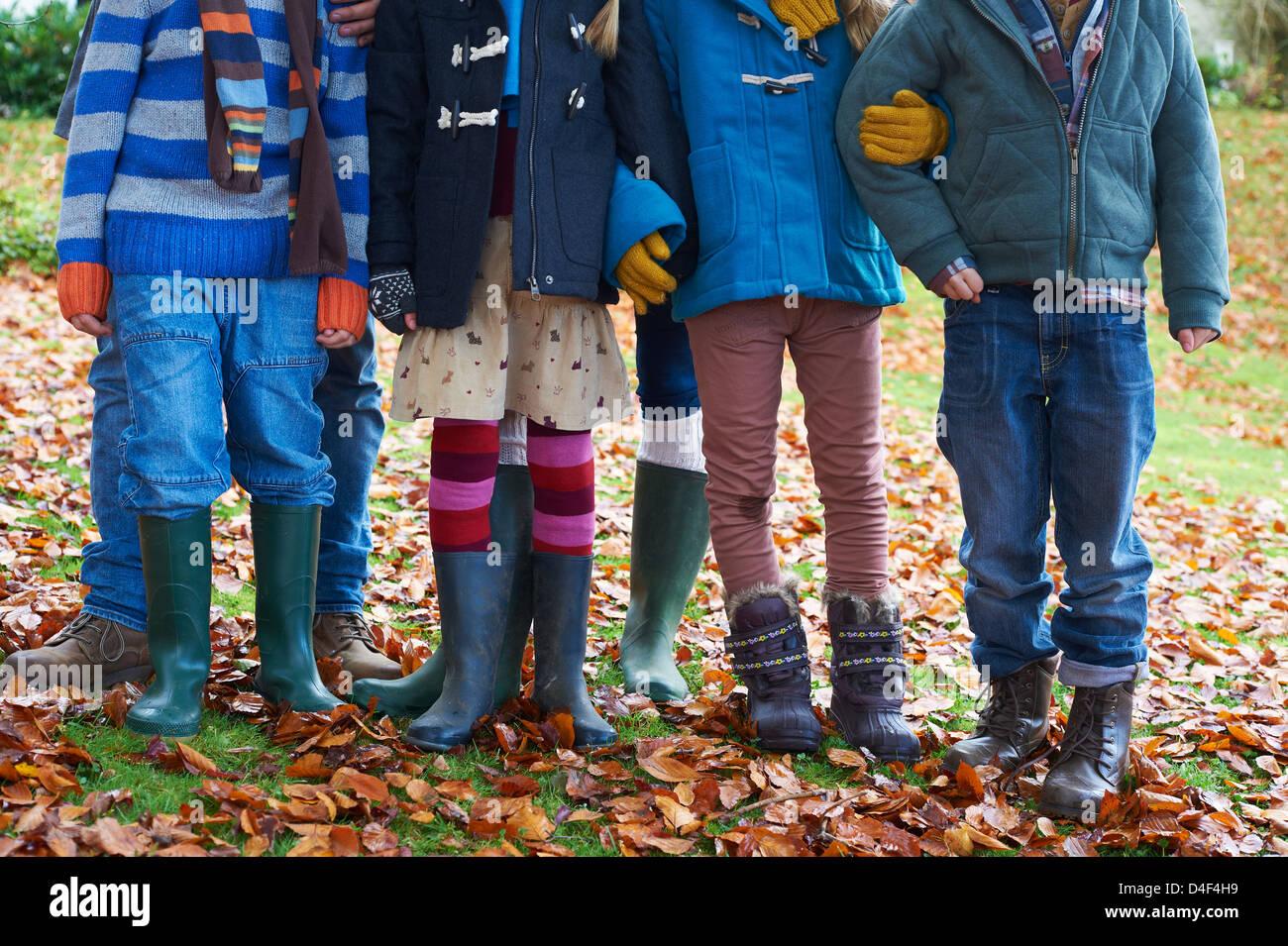 Kinder stehen zusammen im Herbstlaub Stockbild