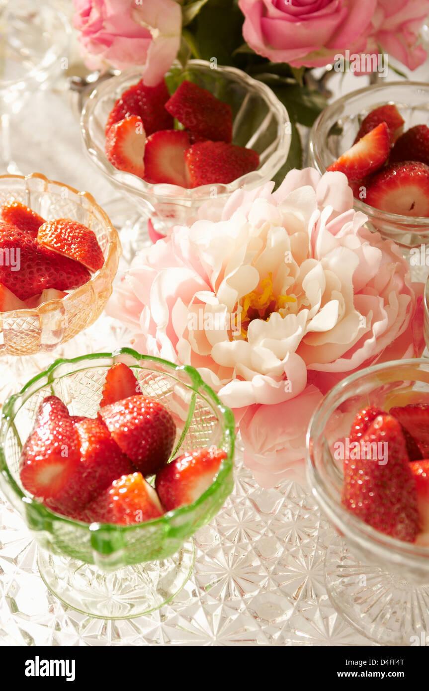 Schalen mit Erdbeeren und Blumen auf Tisch Stockbild
