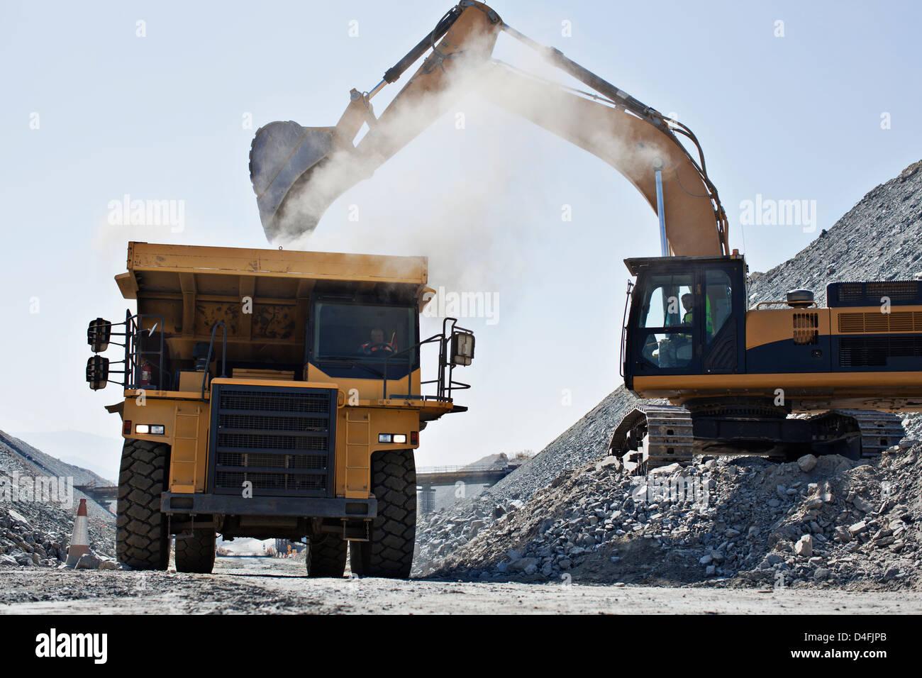 Bagger und LKW arbeiten im Steinbruch Stockbild
