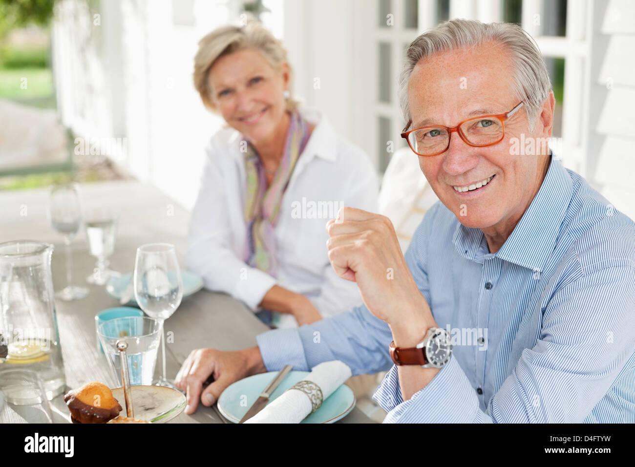 Paar lächelnd am Tisch zusammen Stockbild