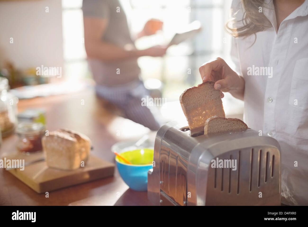 Frau Brot im Toaster weglegen Stockbild