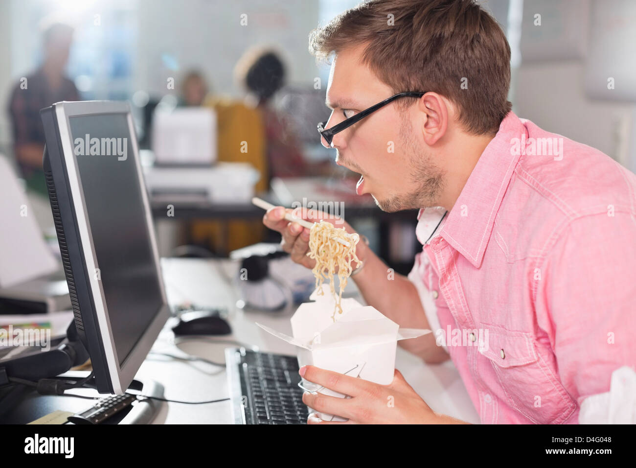 Geschäftsmann, chinesisches Essen am Schreibtisch Stockbild