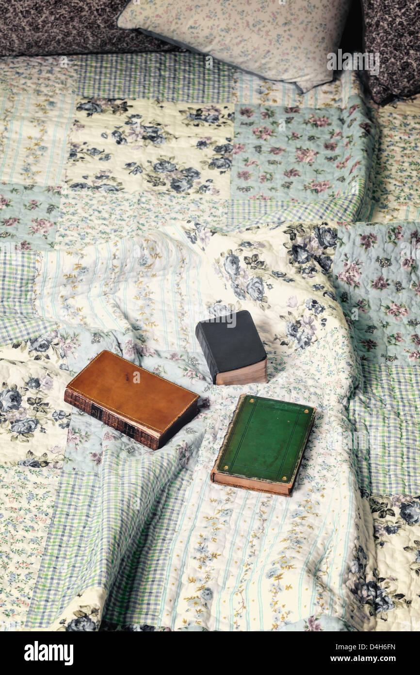 drei alte Bücher auf einem Vintage Bett Stockbild