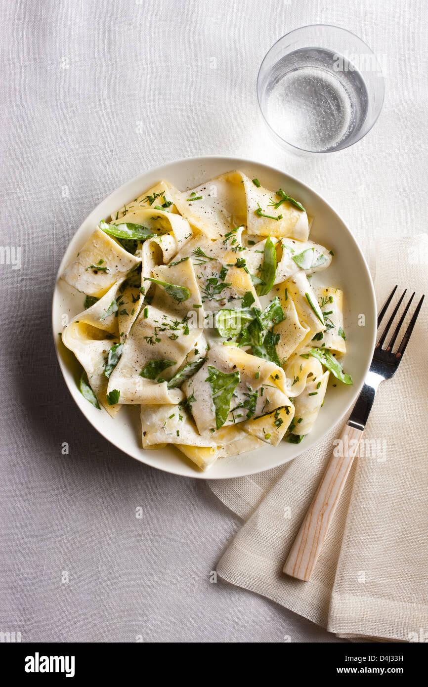 Ein Teller mit Pappardelle Pasta mit cremigem Ricotta, Baby-Spinat, frischen Kräutern und Pfeffer. Stockbild
