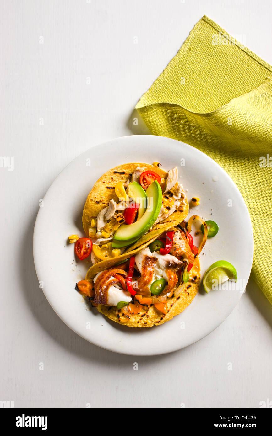 Hühnerfleisch Tacos mit Tomaten, Avocado und gegrilltem Mais + angebraten Tilapia Tacos mit bunten Paprika Stockbild