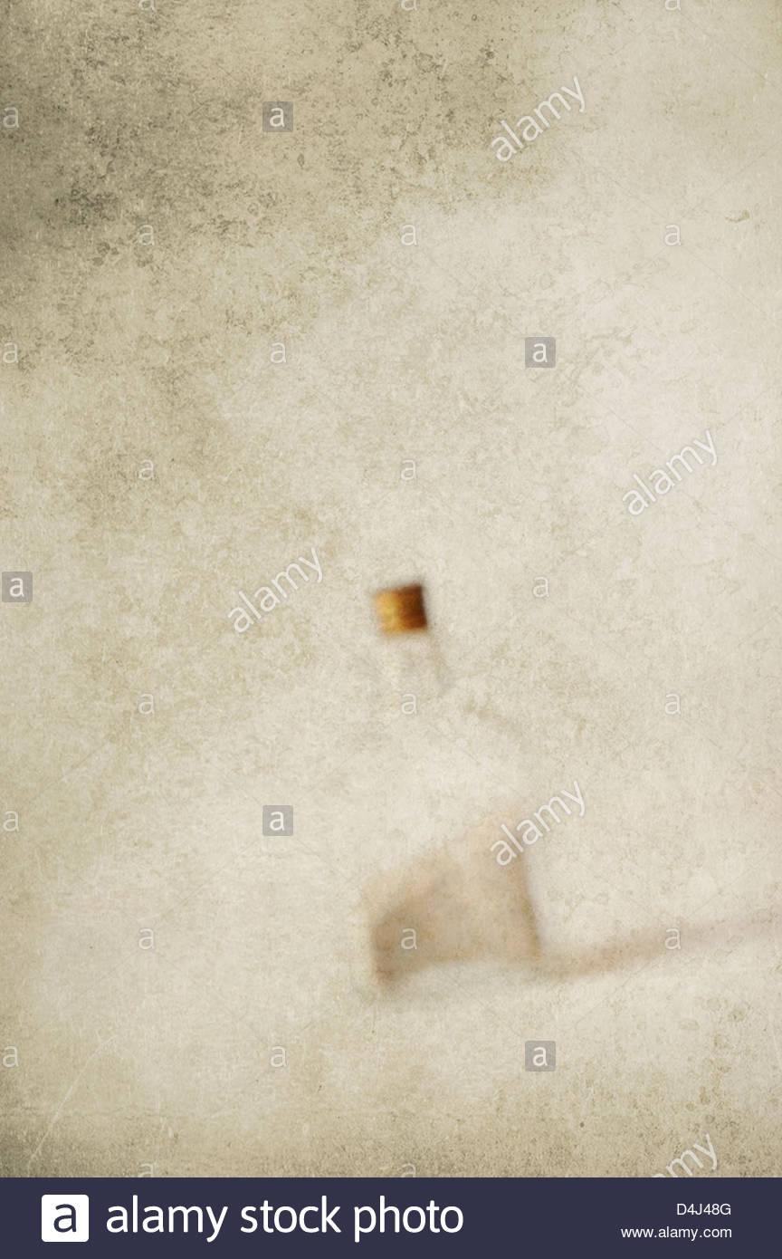 Verschwommenes Bild der Glasflasche gefüllt mit Sand auf strukturierten Hintergrund Stockbild