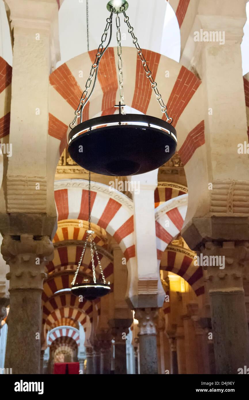 Lampe, dekoriert mit christlichen Kreuz hängt unter den maurischen Bögen der Mezquita Moschee-Kathedrale Stockbild