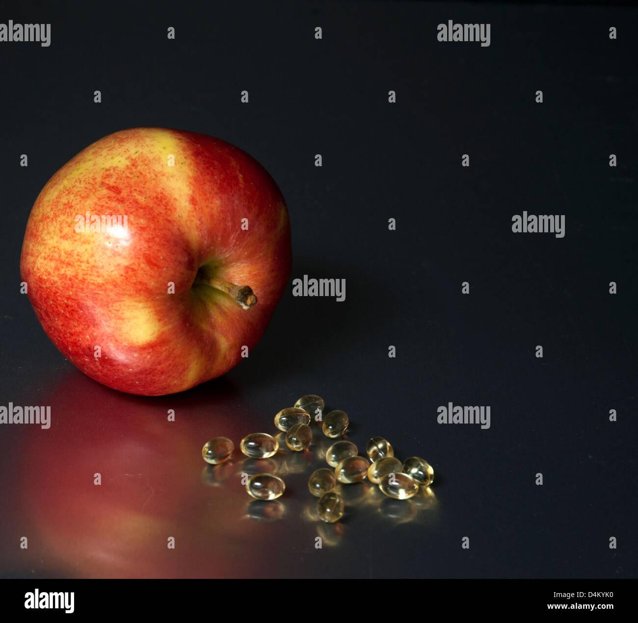 Roter Apfel legen neben Haufen Vitamine Stockbild