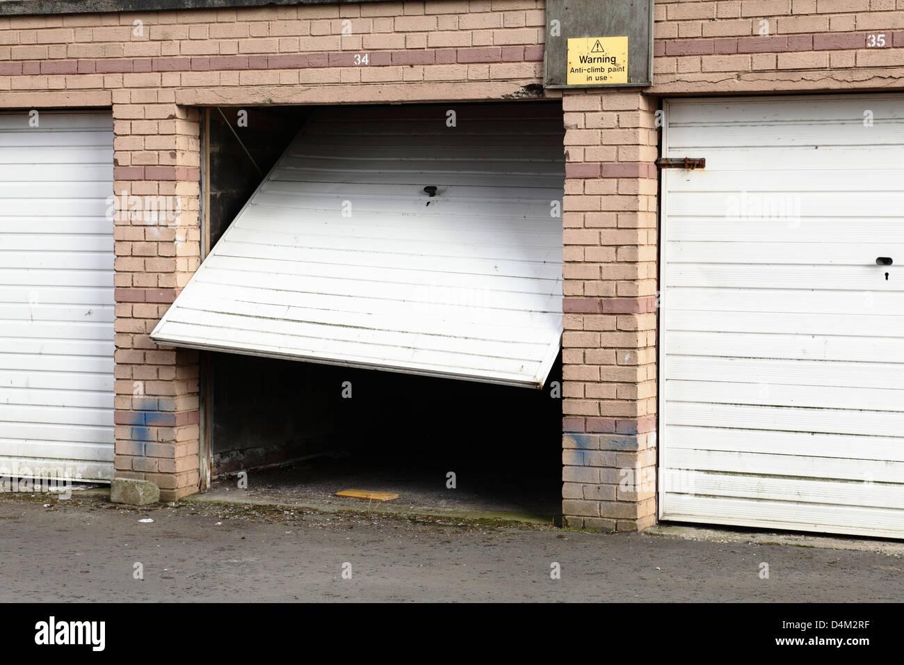 Eine abschließbare Garage mit einer defekten Tür, UK Stockbild