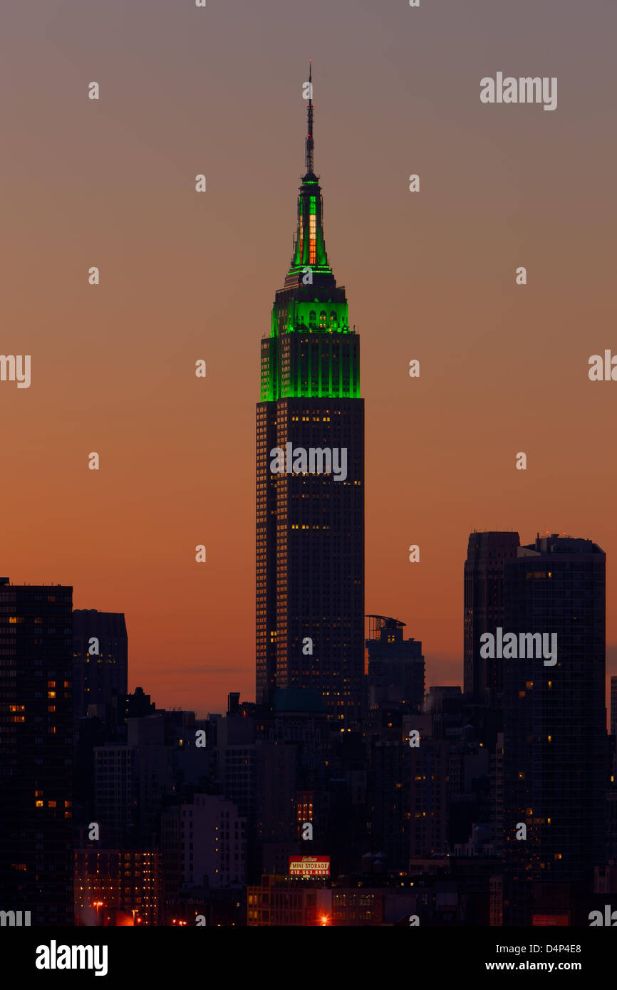 Das Empire State Building in grün leuchtet der Himmel leuchtet orange vor Sonnenaufgang in New York City leuchtet. Stockbild