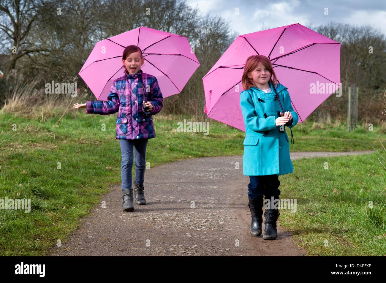 Zwei 8 jährige kaukasische Mädchen mit rosa Schirmen bergauf Stockbild