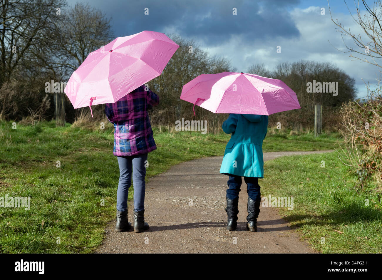 Zwei 8 jährige kaukasische Mädchen zu Fuß entfernt mit rosa Schirme bis Stockbild