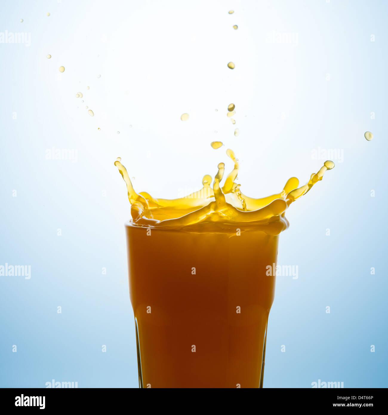 Spritzer auf ein Glas Orangensaft vor einem blauen Hintergrund Stockbild