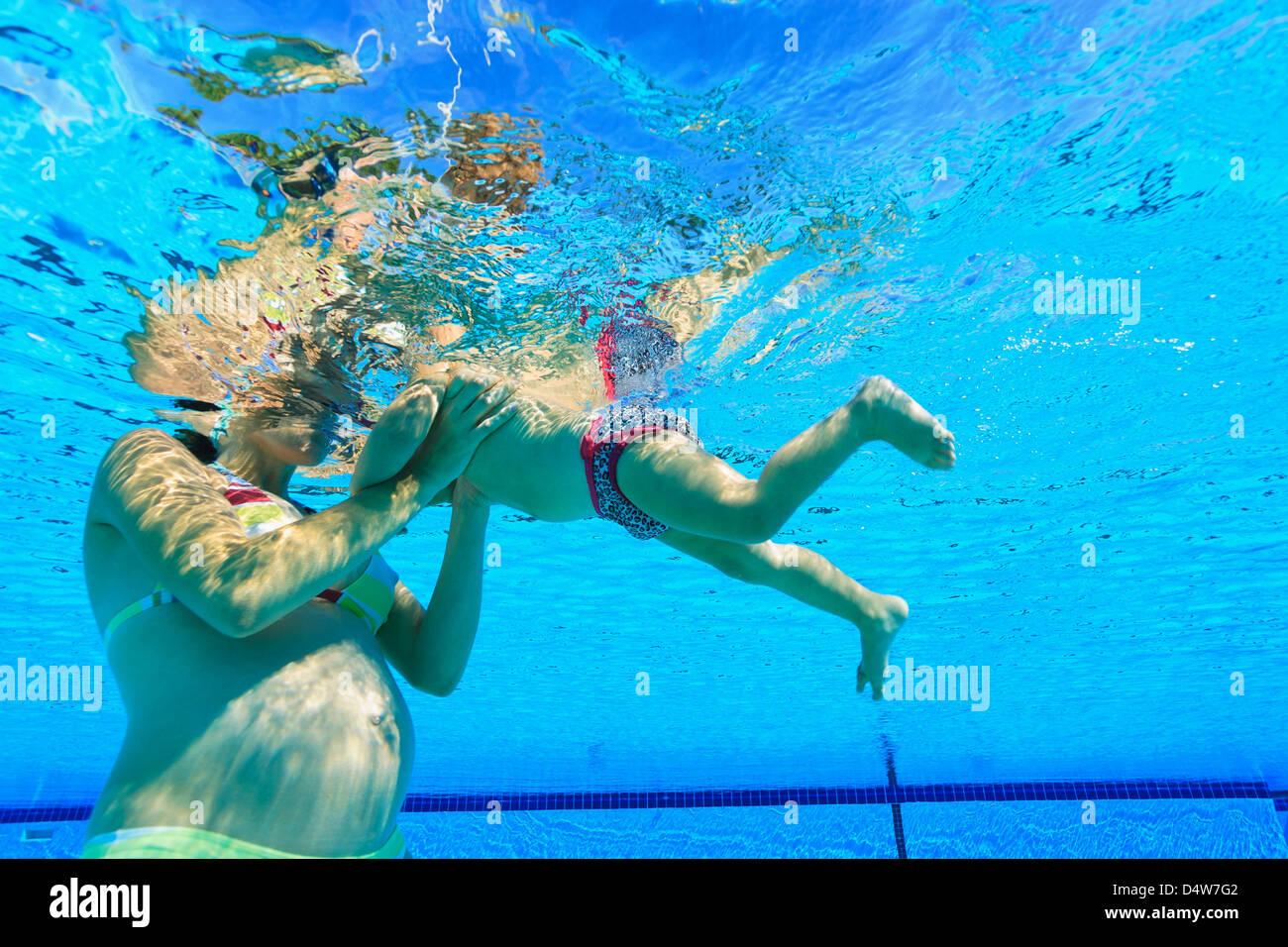 Schwangere Mutter mit Kleinkind im pool Stockbild