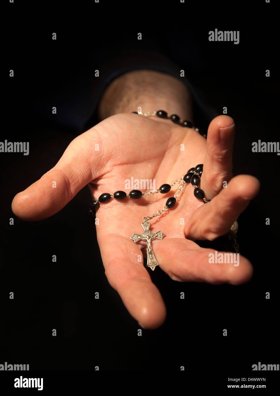 Helfende Hand festhalten Rosenkranz und Kreuz. Stockfoto