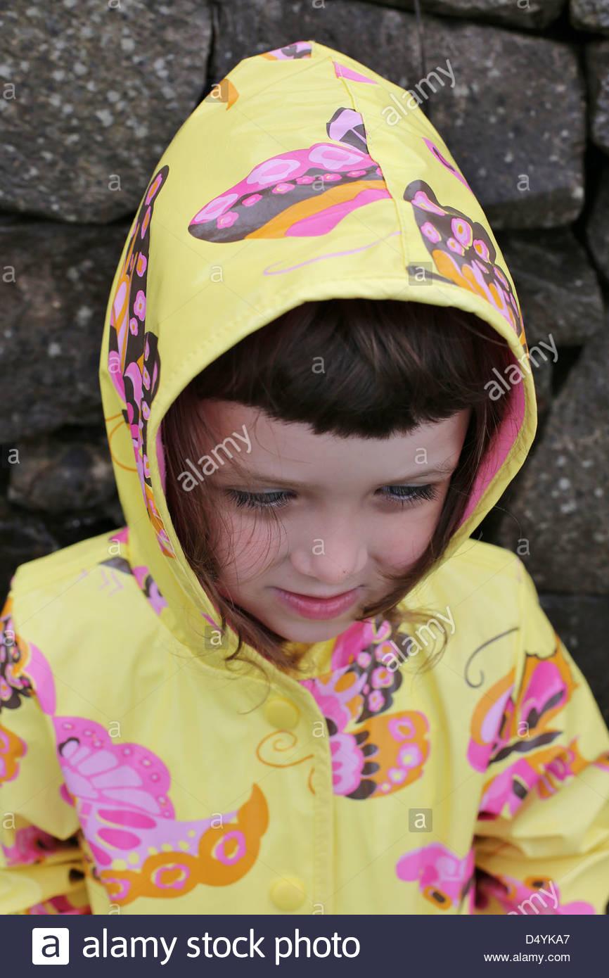 Ein junges Mädchen in einem Regenmantel. Stockbild